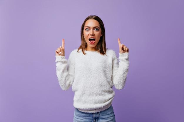 Geschokte, positieve student deed van verbazing haar mond open. brunette meisje met blauwe ogen in witte pluizige trui poseren op geïsoleerde muur met ruimte voor tekst