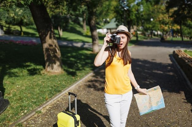 Geschokte reiziger toeristische vrouw in hoed met koffer stadsplattegrond foto's maken op retro vintage fotocamera in de stad buiten. meisje dat naar het buitenland reist om een weekendje weg te reizen. toeristische reis levensstijl.