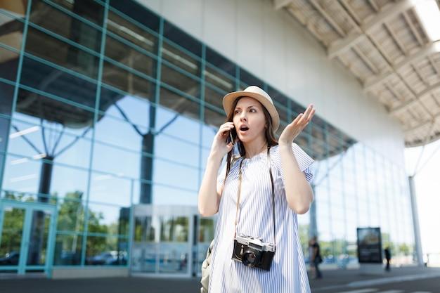 Geschokte reiziger toeristische vrouw met retro vintage fotocamera spreidde handen praten over mobiel telefoongesprek vriend