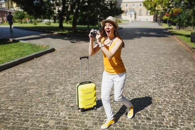Geschokte reizigerstoeristenvrouw in gele vrijetijdskleding met koffer neemt foto's op retro vintage fotocamera die buiten loopt. meisje op weekendje weg naar het buitenland. toeristische reis levensstijl.