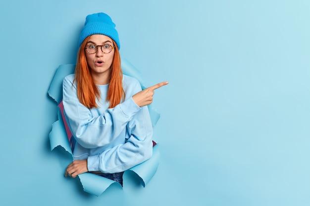 Geschokte roodharige jonge vrouw houdt de adem in staart afgeluisterde ogen wijst weg op kopie ruimte staat in gescheurd gat draagt blauwe hoed en trui toont iets van hoge prijs op item