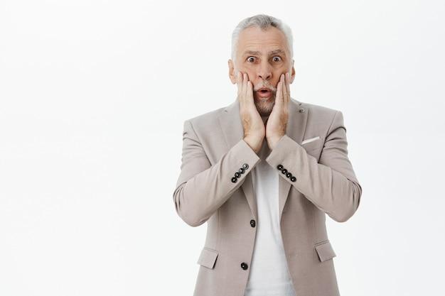 Geschokte senior man in pak keek verbaasd, hijgend verbaasd