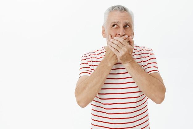 Geschokte senior man sloot bezorgd zijn mond en keek in de linkerbovenhoek