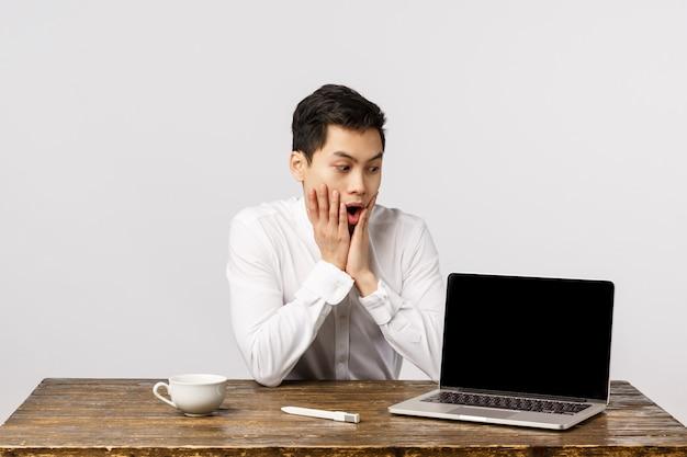 Geschokte, sprakeloze, verbaasde aziatische kantoorjongen zit aan het werk op het werk, reageert geschokt en verrast als kijkend laptopdisplay, iets verbluffends, super promotie op het scherm