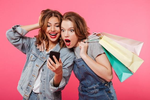 Geschokte twee vrouwenvrienden die het winkelen zakken houden gebruikend mobiele telefoon.