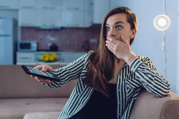 Geschokte, verbaasde, bange vrouw die thuis een horrorfilm kijkt