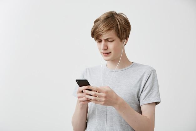 Geschokte, verbaasde hipster-man-berichten met vrienden, gebruikt gratis internetverbinding op moderne mobiele telefoon, ontvangt slecht nieuws. verbaasd jong mannetje krijgt slecht nieuws. menselijke gevoelens, emoties, reactie