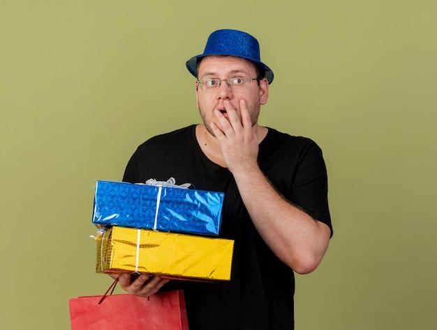 Geschokte volwassen slavische man met optische bril met blauwe feestmuts legt hand op gezicht met geschenkdozen en papieren boodschappentas and