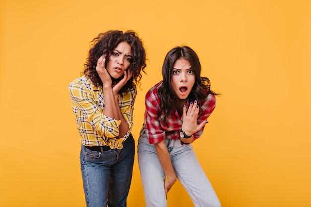 Geschokte vriendinnen kijken met verontwaardiging en overtuiging. meisje in rode blouse opende verrast haar mond.