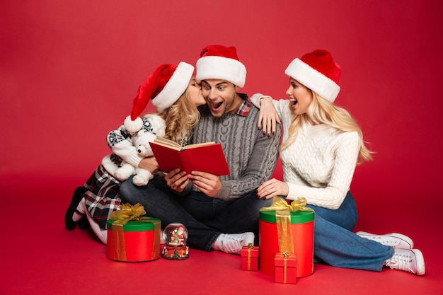 Geschokte vrolijke jonge familie die kerstmishoeden dragen die boek lezen.