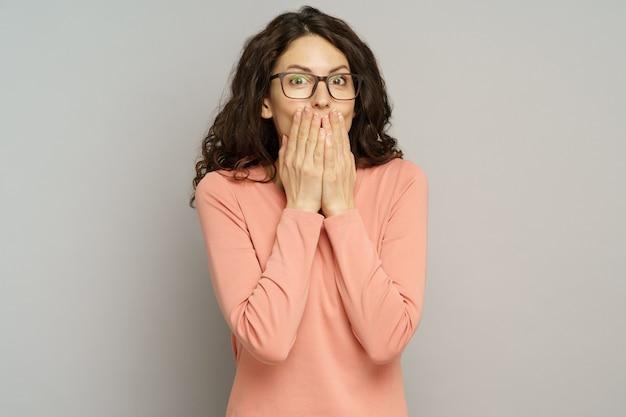 Geschokte vrouw bedekt open mond met handen om roddelportret van verraste duizendjarige vrouw te stoppen