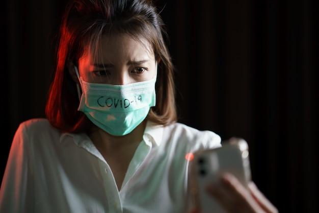 Geschokte vrouw die beschermend masker draagt dat smartphone gebruikt