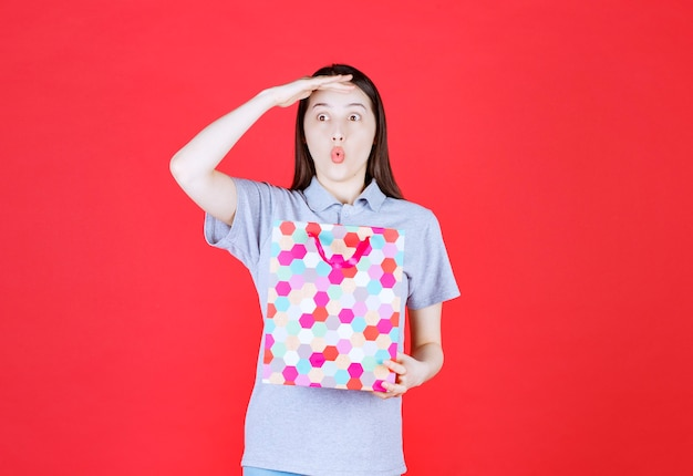 Geschokte vrouw die een kleurrijke boodschappentas vasthoudt en wegkijkt