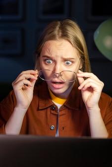 Geschokte vrouw die haar laptop bekijkt