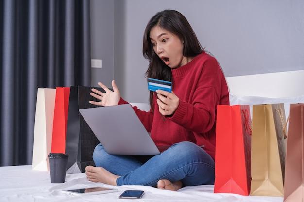Geschokte vrouw die laptop voor online het winkelen met creditcard op bed met behulp van