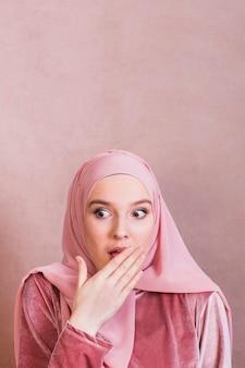 Geschokte vrouw die lippen behandelen met palm tegen gekleurde achtergrond