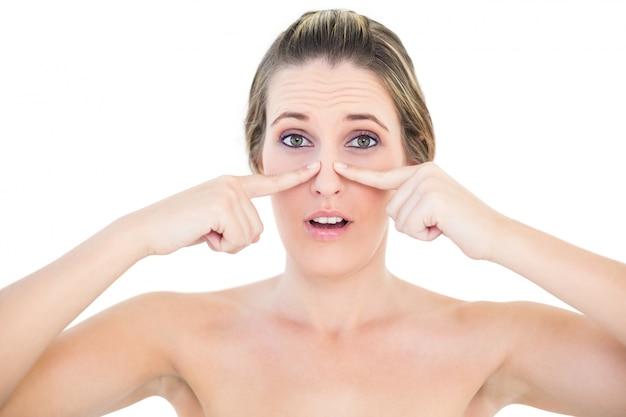 Geschokte vrouw die meeëter op haar neus drukt