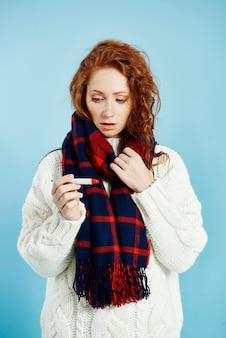 Geschokte vrouw die met digitale thermometer temperatuur controleert