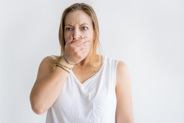 Geschokte vrouw die mond behandelt met hand