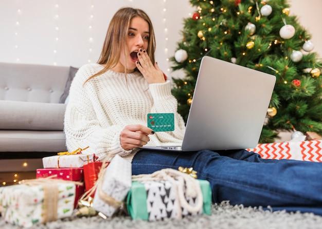 Geschokte vrouw die online bij kerstboom winkelt