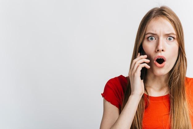 Geschokte vrouw die op haar telefoon met exemplaarruimte spreekt