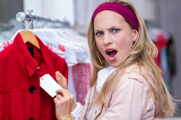 Geschokte vrouw die prijskaartje toont aan camera