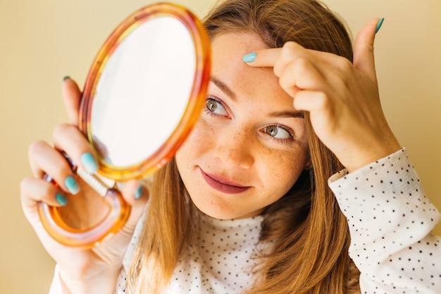 Geschokte vrouw die puistje op voorhoofd in spiegel bekijkt.