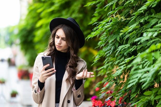 Geschokte vrouw die verrassend nieuws op slimme telefoon in de straat vindt