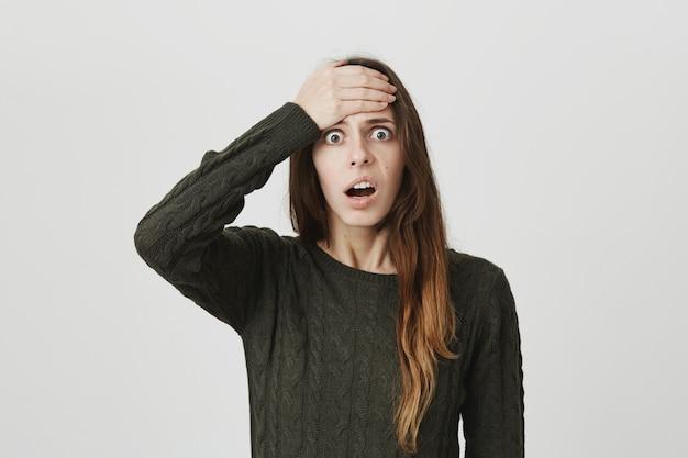 Geschokte vrouw herinnert zich iets, slaat voorhoofd en staart camera