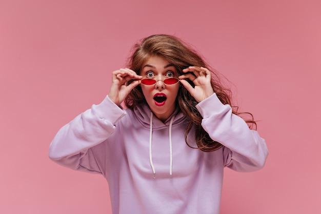 Geschokte vrouw in paarse oversized hoodie zet rode zonnebril af