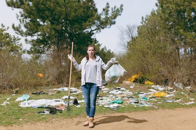 Geschokte vrouw in vrijetijdskleding die vuilniszakken en hark vasthoudt voor het ophalen van afval in een bezaaid park