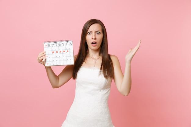 Geschokte vrouw in witte jurk spreidt handen met vrouwelijke menstruatiekalender voor het controleren van menstruatiedagen