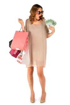 Geschokte vrouw in zonnebril met kleurrijke boodschappentassen kijken naar geld