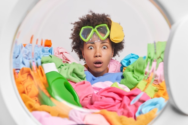 Geschokte vrouw met krullend haar die thuis de was doet, doet dagelijkse huishoudelijke klusjes poses in de wasmachine met vuile kleren rond draagt een snorkelbril op het voorhoofd en is enorm verrast