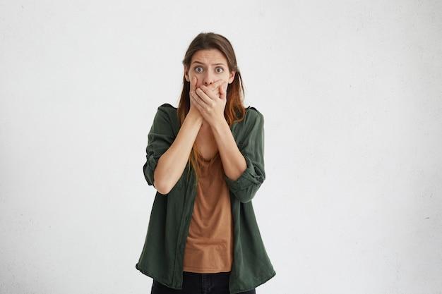 Geschokte vrouw met lang geverfd haar in groene kleren kijken met afgeluisterde ogen die haar mond bedekken met handen die wanhopig kijken terwijl ze proberen stil te blijven en niemand geheimen vertellen