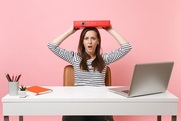 Geschokte vrouw met rode map met papieren document op hoofd en bezig met project terwijl ze op kantoor zit met laptop