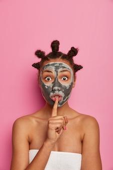 Geschokte vrouw van gemengd ras maakt zwijggebaar, vertelt geheim van schoonheid, brengt kleimasker aan op gezicht om rimpels te verminderen, poseert tegen roze muur, blijft lang jong. huidverzorgingsroutine