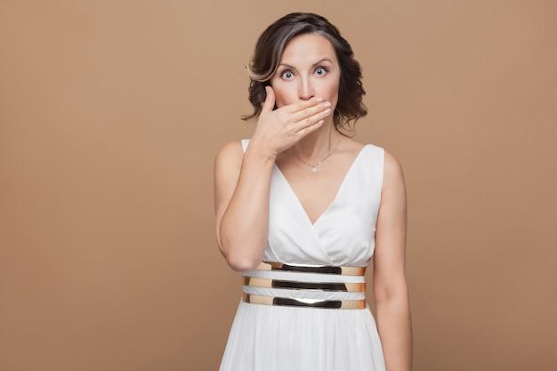Geschokte vrouw van middelbare leeftijd met grote ogen gesloten mond. emotioneel uitdrukkende vrouw in witte jurk, rode lippen en donker krullend kapsel. studio-opname, binnen, geïsoleerd op beige of lichtbruine achtergrond