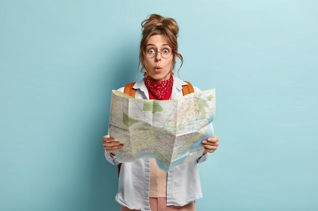 Geschokte vrouwelijke europese toerist reist de wereld rond, verrast om los te lopen, leest kaart