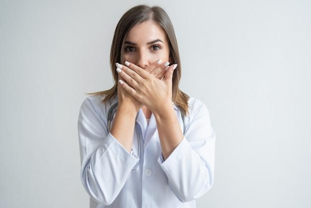 Geschokte vrouwelijke kaukasische specialist in laboratoriumlaag die mond behandelt