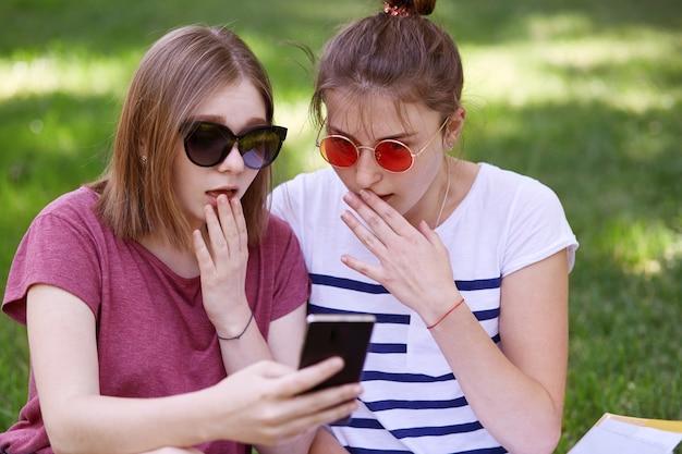Geschokte vrouwelijke tieners kijken verrassend naar smartphone, ontvangen onverwachte boodschap, dragen trendy zonnebril
