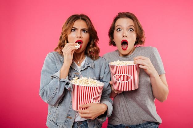 Geschokte vrouwen vrienden eten popcorn kijken film