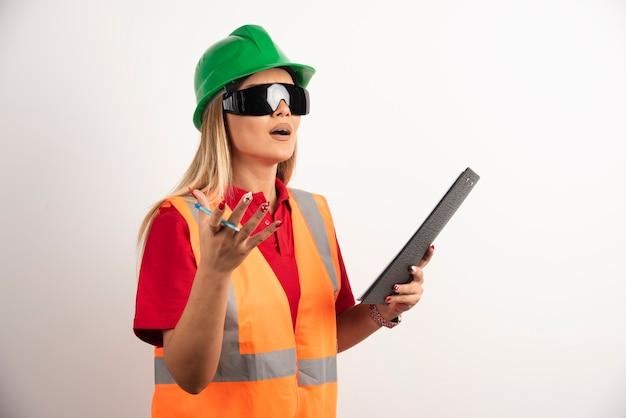 Geschokte vrouwenarbeider die een klembord houdt.