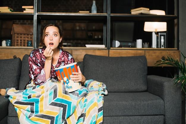 Geschokte vrouwenzitting op bank met popcorn het letten op televisie