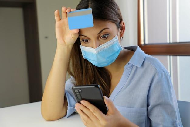 Geschokte wanhopige bedrijfsvrouw die met chirurgisch masker op mobiele telefoon kijkt beklemtoonde haar creditcardverklaring.