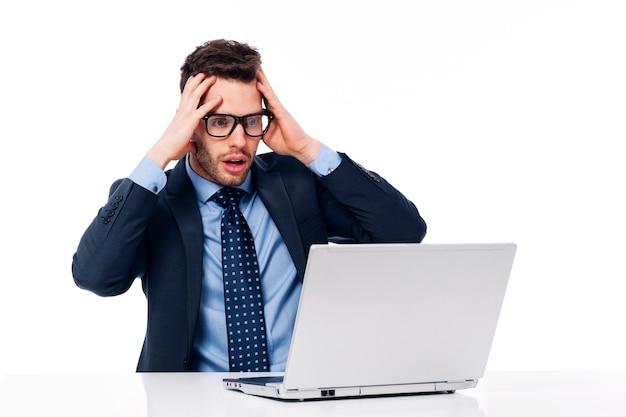 Geschokte zakenman die laptop bekijkt