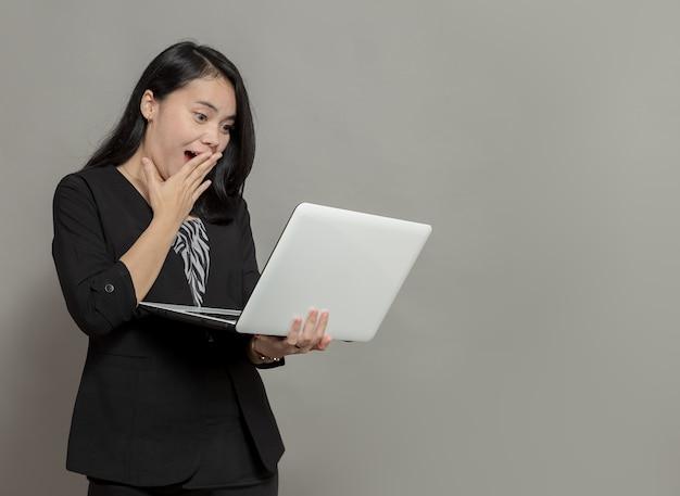 Geschokte zakenvrouw die laptopscherm vasthoudt en bekijkt