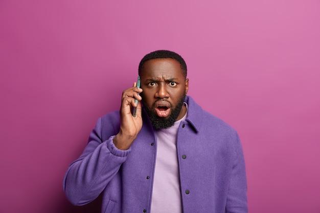 Geschokte zwarte man staart in paniek, hoort slecht nieuws tijdens telefoongesprek, hijgt van verwondering, fronst zijn wenkbrauwen en kijkt zenuwachtig, draagt paars jasje