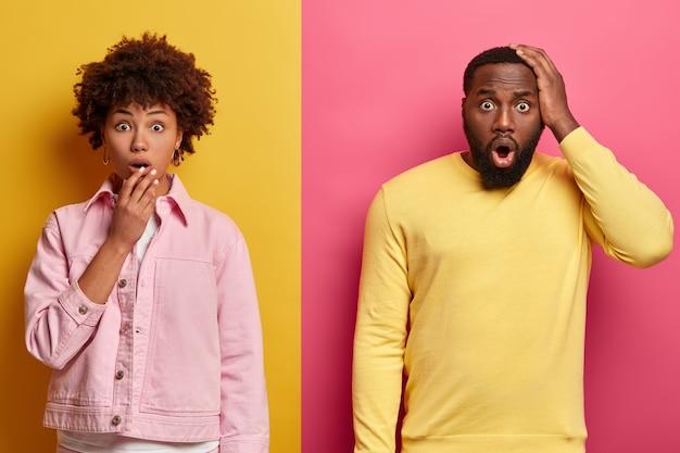 Geschokte zwarte vrouw en man staren naar de camera, drukt grote verrassing uit, opent mond, hoort ongelooflijk nieuws, draagt pastelroze en gele kleding