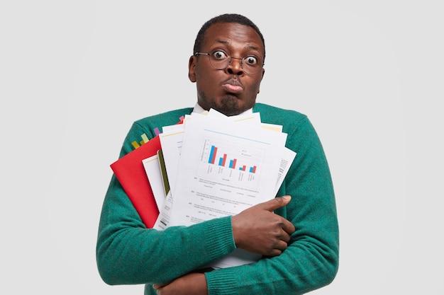 Geschokte zwarte zakenman houdt papieren met grafieken vast, pruilt lippen, voelt zich verbluft door veel werk, draagt documentatie bij zich, staart door een bril
